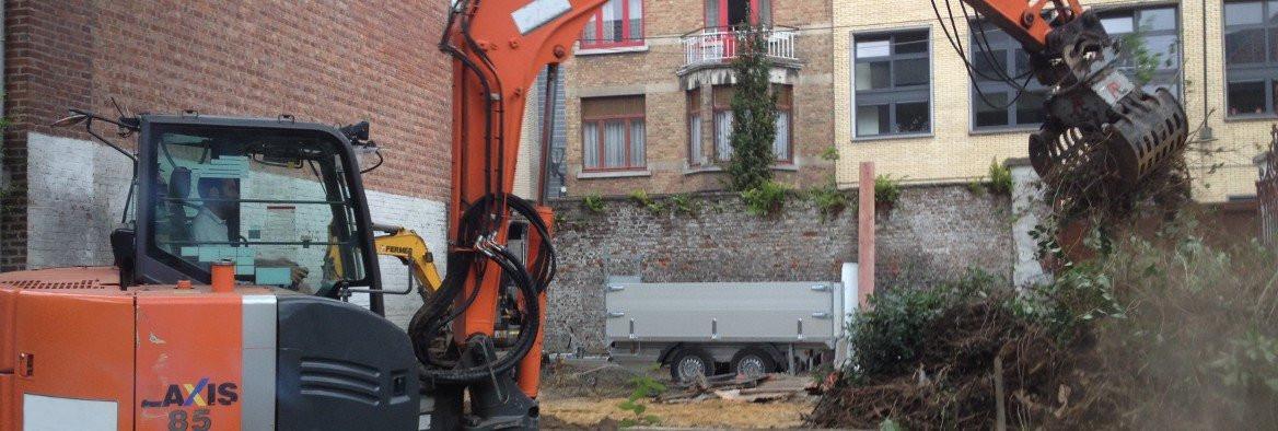 Een graafmachine verwijdert struiken tijdens de aanleg van een tuin